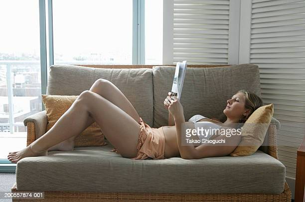 Young woman reading on sofa, side view