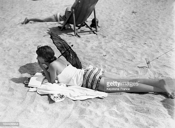 A young woman reading on the beach in Deauville around 19201930