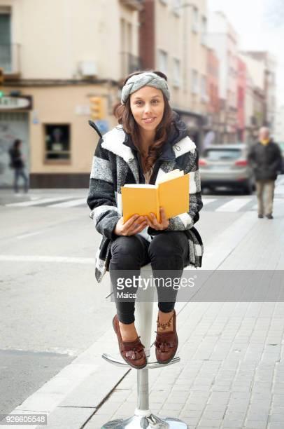 Junge Frau auf der Straße lesen