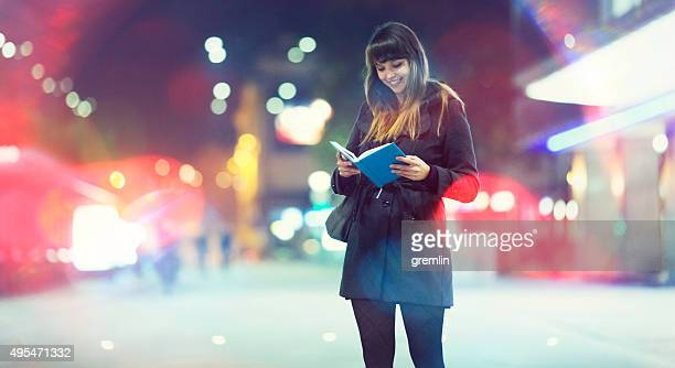 Young woman reading on the street, waiting