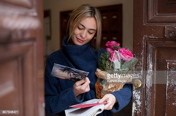 young woman reading postcard, holding flowers