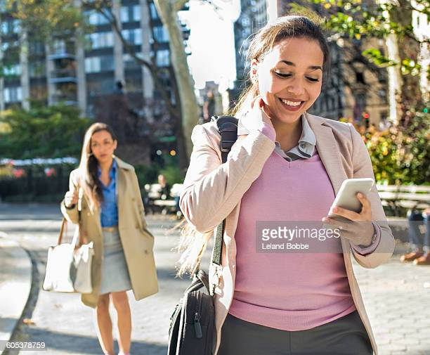 Young woman reading smartphone texts whilst walking through city park