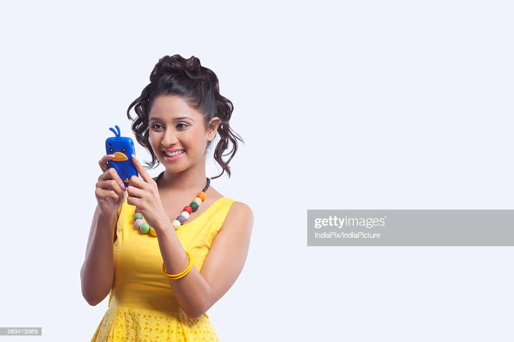 Young woman reading sms on mobile phone : Stock Photo