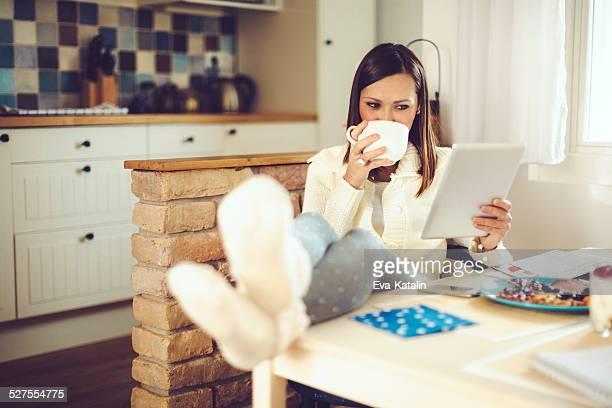 Mujer joven lectura comprimido y de su desayuno en la cocina