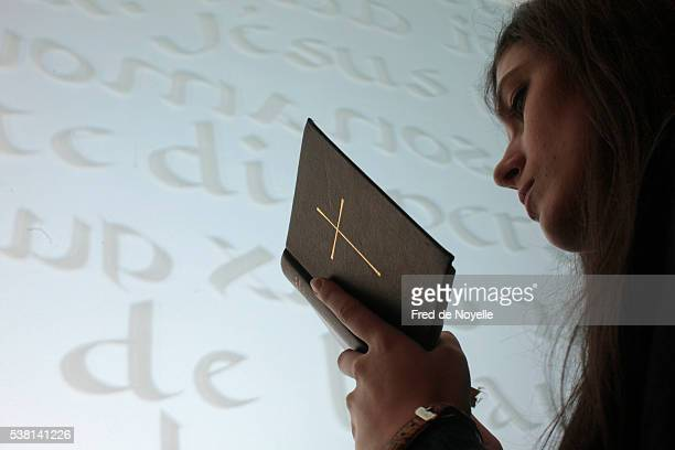 Young woman reading the bible in a church