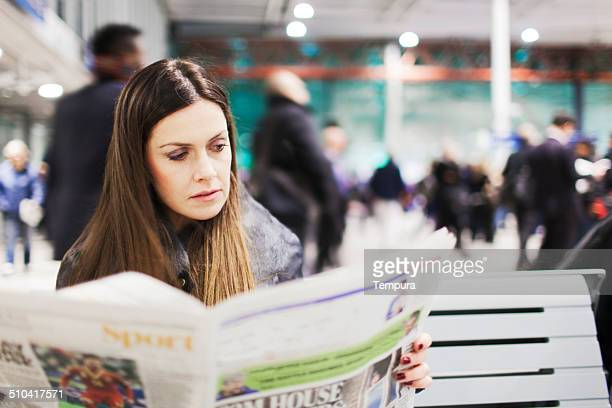 Young woman reading the newspaper on a train station.