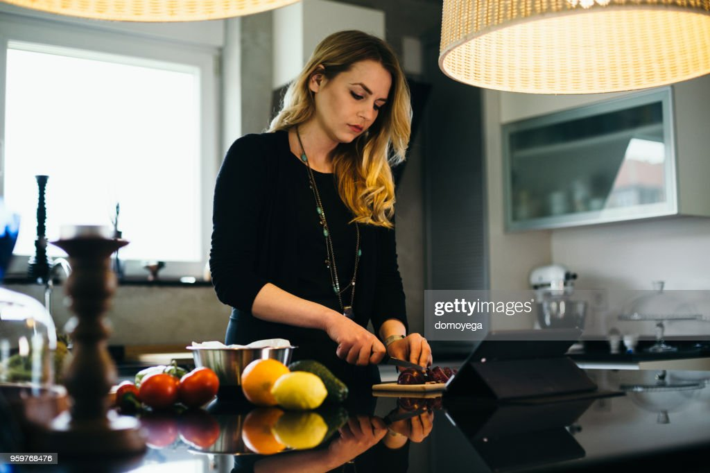 Junge Frau, lesen das Rezept von einer digital-Tablette und eine Mahlzeit zuzubereiten : Stock-Foto