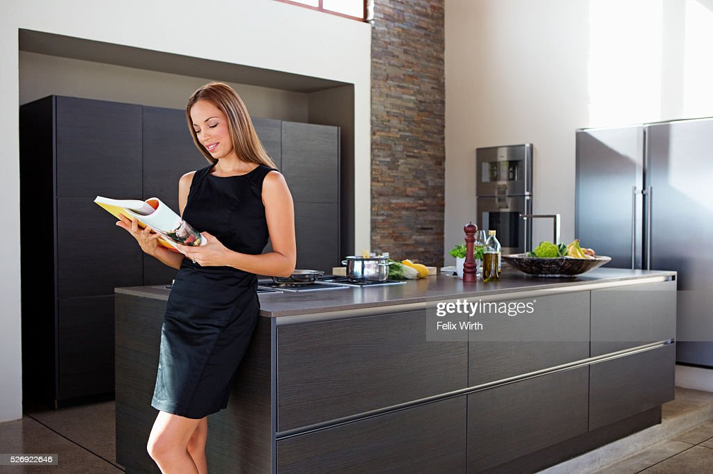 Young woman reading while cooking dinner : Stock-Foto