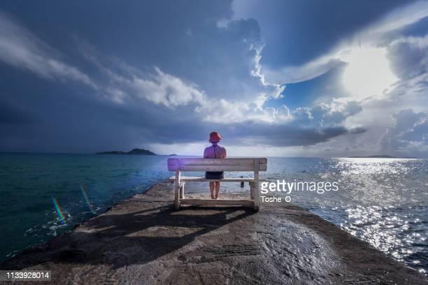 la jeune femme lit un livre sur un banc dans un port près de la mer avec le ciel dramatique dans l'backgroung - personnage imaginaire photos et images de collection