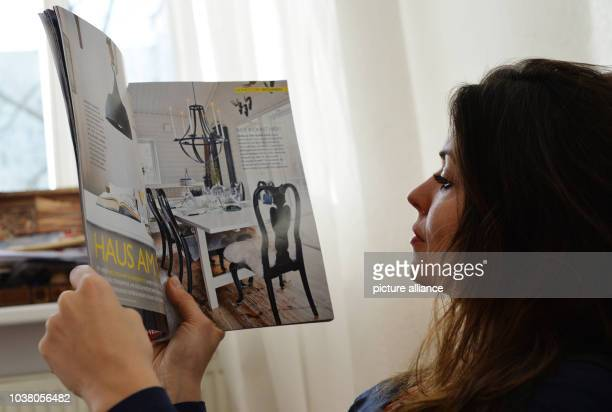 A young woman reads a magazine about interior design in Berlin Germany 02 December 2013 Photo Jens Kalaene MODEL RELEASED | usage worldwide
