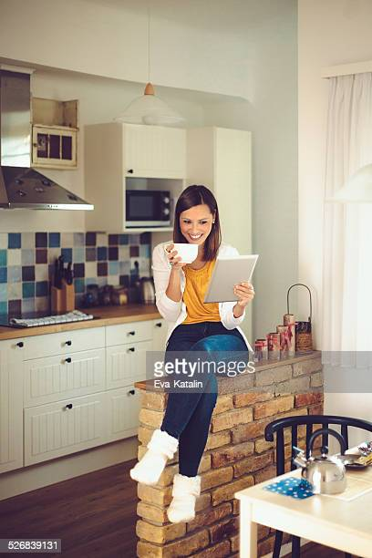 Young woman reads a tablet while drinking coffee