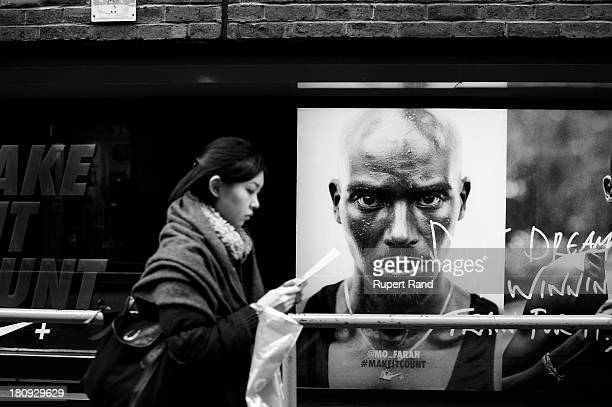 CONTENT] A young woman reads as she walks past a photo of Mo Farah in Covent Garden