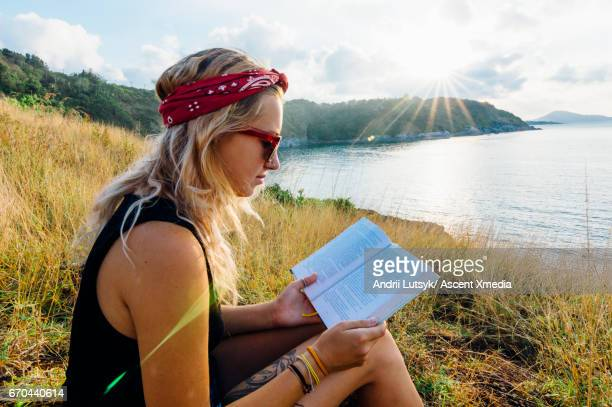 Young woman reads book, on hillside above sea