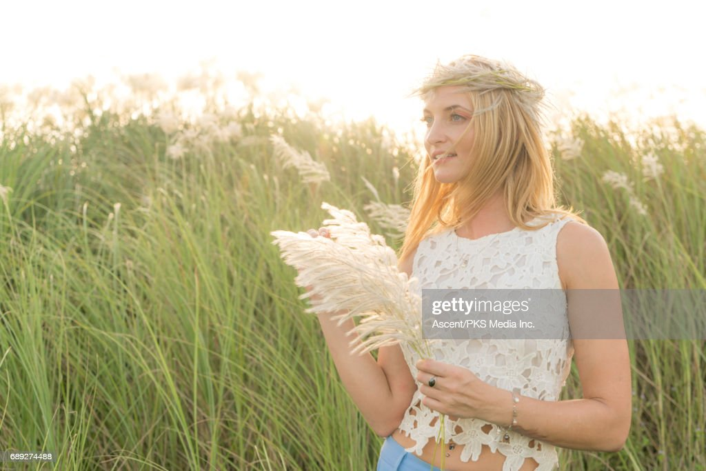 Young woman reads book, on hillside above sea : Stock Photo