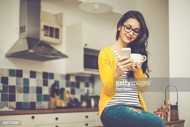 Young woman reads her messages while drinking coffee
