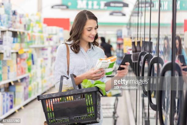 young woman reads label on frozen food product - frozen food stock pictures, royalty-free photos & images