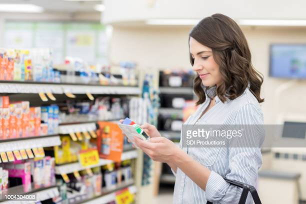 若い女性が薬局で薬ラベルを読み込む