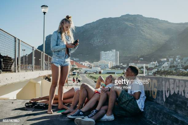 Young woman reads mobile phone to group of friends