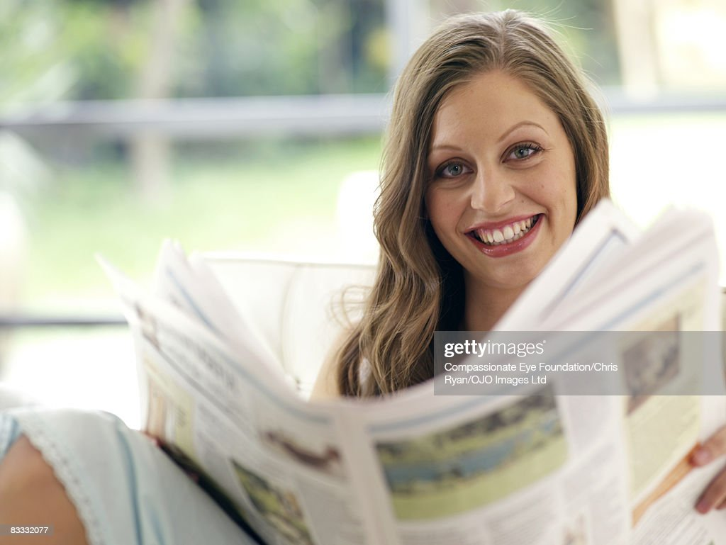 Young woman reads newspaper : Stock Photo
