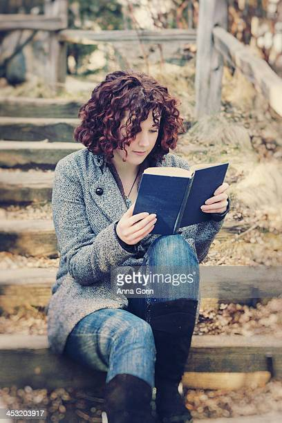 Young woman reads outdoors on stairs
