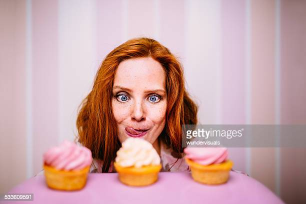 young woman really wants to eat cupcakes - lust girl stock photos and pictures