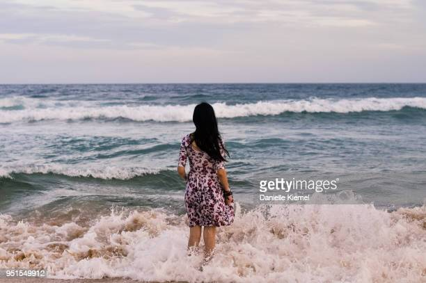 young woman, rear view, standing in water at beach - femme brune de dos photos et images de collection