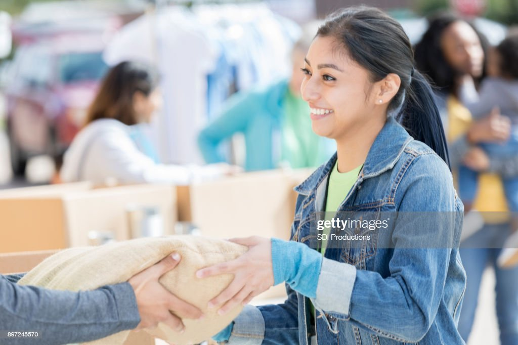 Young woman receives a bag of food during food drive : Stock Photo