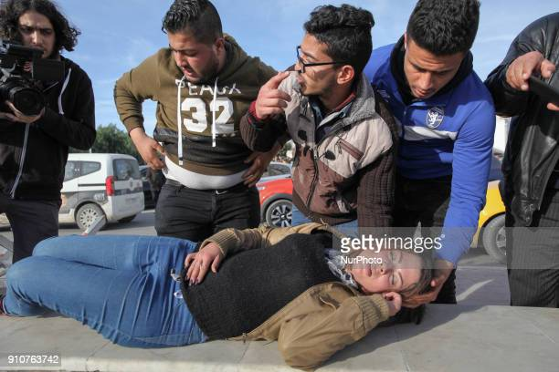A young woman receives first aid after she fainted during clashes erupted between security forces and protesters as they demonstrated outside the...