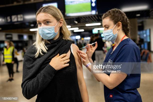 Young woman receives the Covid-19 vaccine at a walk-in vaccine clinic taking place at the Tottenham Hotspur Stadium on June 20, 2021 in London,...