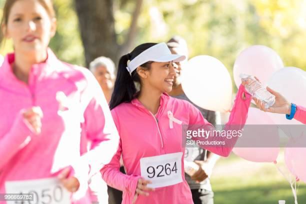 young woman receives water during charity run - social awareness symbol stock photos and pictures
