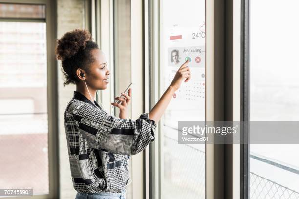 Young woman receiving a call on windowpane with world map in office