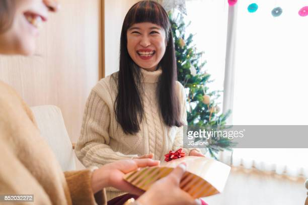 Young woman receiving a Christmas present from her friend