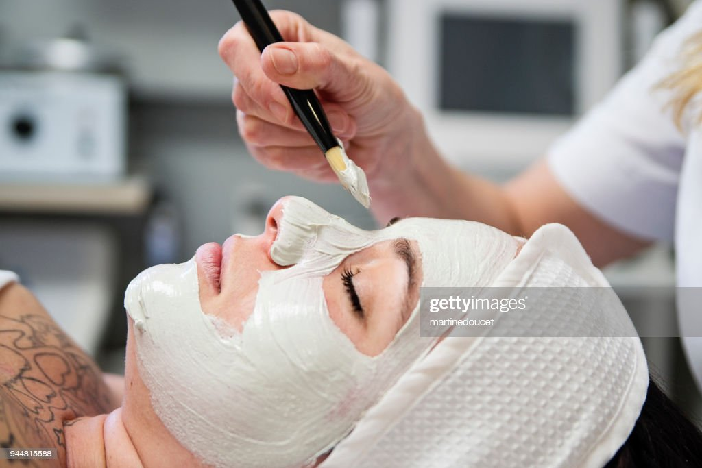 Young woman receiving a facial treatment in beauty spa. : Stock Photo