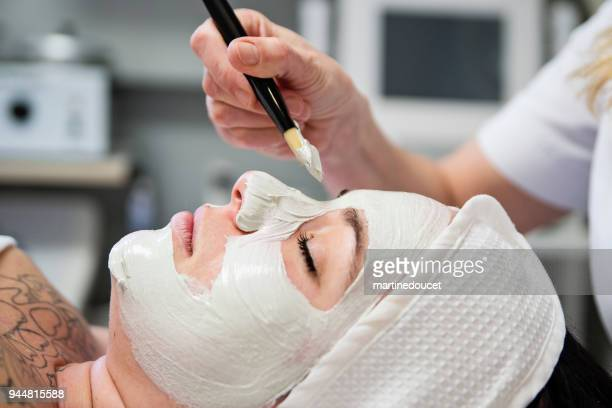 """young woman receiving a facial treatment in beauty spa. - """"martine doucet"""" or martinedoucet stock pictures, royalty-free photos & images"""