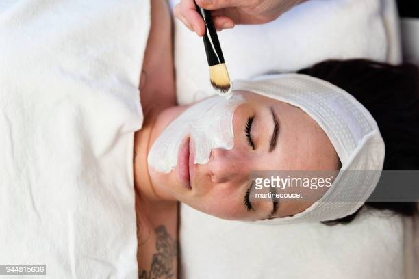 Young woman receiving a facial treatment in beauty spa.