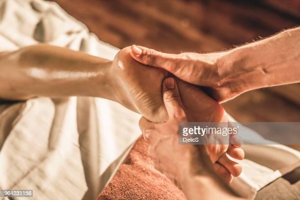 joven mujer recibiendo un masaje de pie primer plano. - masaje hombre fotografías e imágenes de stock