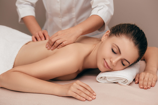young woman receiving a massage at spa salon 1007420070