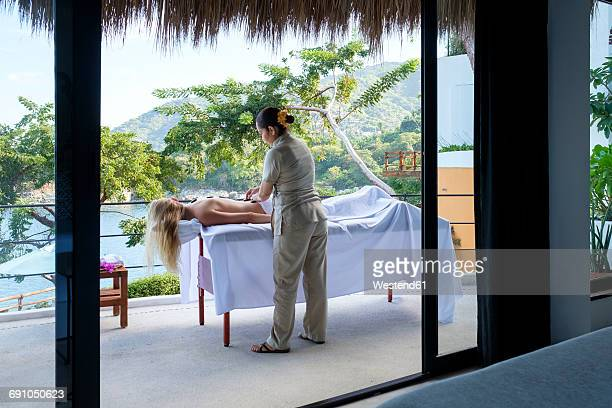 Young woman receiving a massage on the balcony of her suite in a luxury vacation retreat