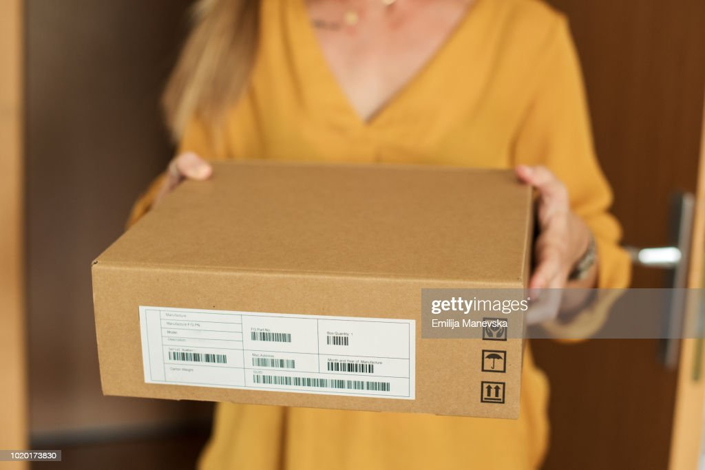Young woman receiving a package : ストックフォト