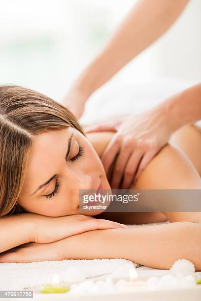 Young woman receiving back massage at spa.