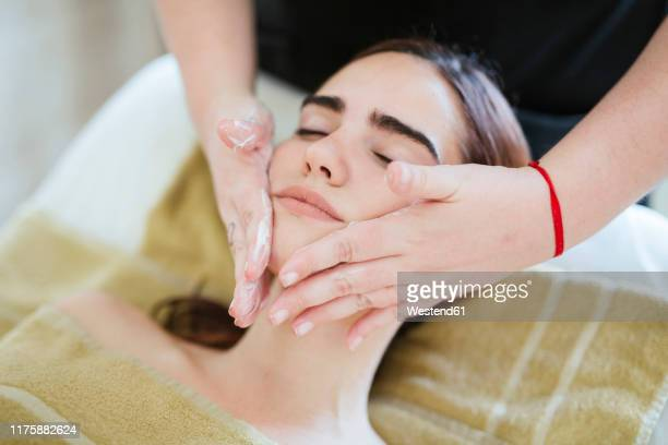 young woman receiving facial beauty treatment in a spa - massage room photos et images de collection