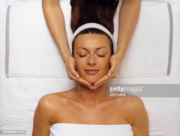 young woman receiving facial, eyes closed, overhead view - kosmetische behandlung stock-fotos und bilder