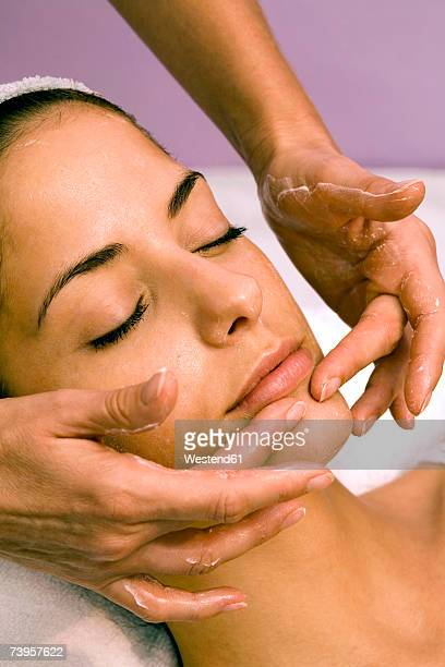 Young woman receiving facial massage, eyes closed, close-up