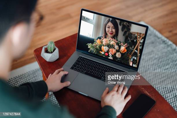 young woman receiving flower bouquet while having a video call with her love - laptop stock pictures, royalty-free photos & images