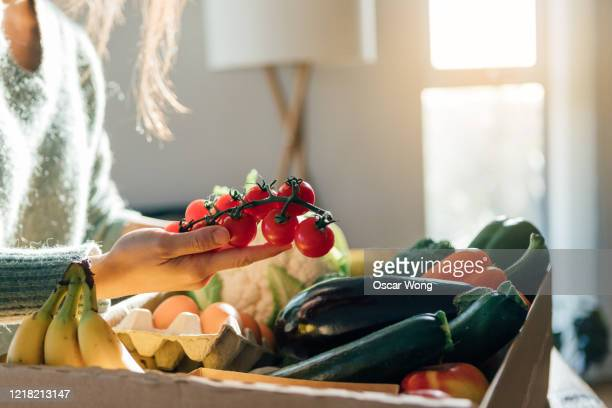 young woman receiving fresh food home delivery - vegetable stock pictures, royalty-free photos & images