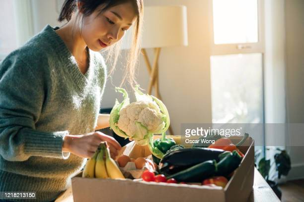 young woman receiving fresh food home delivery - healthy eating stock pictures, royalty-free photos & images