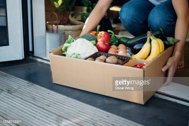young woman receiving fresh food home delivery - fruit stock pictures, royalty-free photos & images