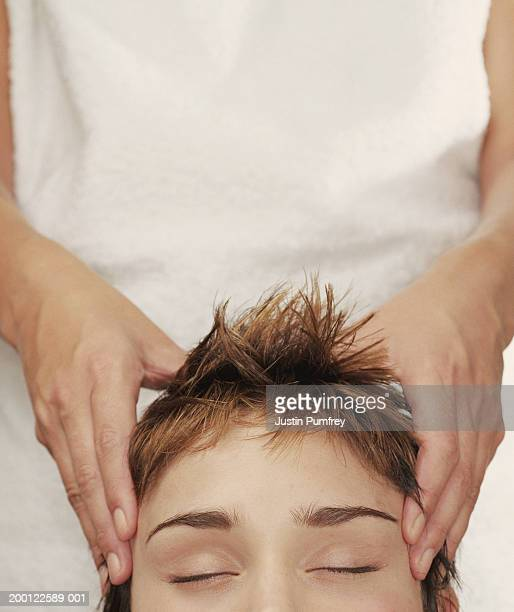 Young woman receiving head massage, close-up