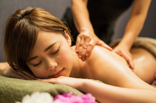 Young woman receiving oil massage 696197724