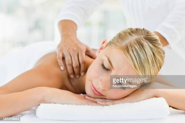 Young woman receiving shoulder massage at spa